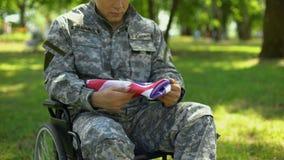 Soldado deficiente que guarda a bandeira americana nas mãos que sentam-se na cadeira de rodas, patriota vídeos de arquivo