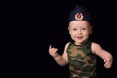 Soldado del bebé en uniforme en un fondo negro El muchacho en las FO Imágenes de archivo libres de regalías