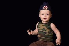 Soldado del bebé en uniforme en un fondo negro El muchacho en las FO Imagenes de archivo