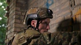 Soldado del ejército que toma objetivo con el arma de la pistola en el edificio almacen de metraje de vídeo