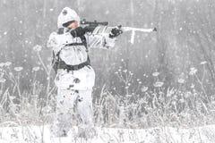 Soldado del hombre en el invierno en una caza con un rifle de francotirador en el camuflaje blanco del invierno que apunta la sit imagenes de archivo