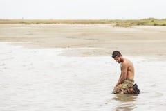 Soldado descamisado de arrodillamiento en la agua de mar Foto de archivo libre de regalías