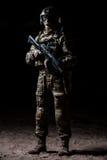 Soldado en camuflaje con un rifle que se coloca en un pelotón y los relojes Fotos de archivo