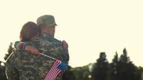 Soldado en el camoubackgrounde que abraza a la hija al aire libre, visión trasera almacen de metraje de vídeo