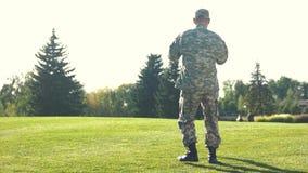 Soldado en el camoubackgrounde que hace girar a su hija alrededor en el parque metrajes