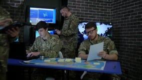 Soldado en uniforme del camuflaje, mapas de la visión y el trabajo en el laptoop, jefaturas militares, informando en sitio de la  almacen de metraje de vídeo