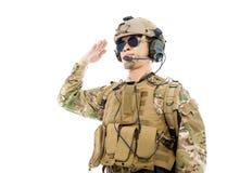Soldado en uniforme militar que saluda sobre el fondo blanco Fotos de archivo