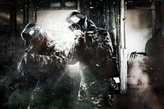 Soldado enmascarado pesadamente armado de dos Paintball en fondo apocalíptico de los posts Concepto del anuncio Fotos de archivo