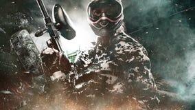 Soldado enmascarado pesadamente armado de Paintball en fondo apocalíptico de los posts E metrajes