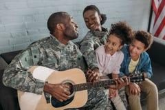 Soldado fêmea afro-americano e crianças que escutam para genar na roupa da camuflagem foto de stock royalty free
