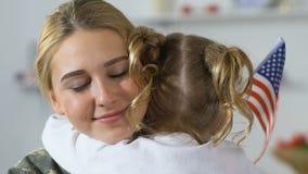 Soldado fêmea feliz que abraça a criança que guarda a bandeira americana, família patriótica, orgulho filme
