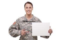 Soldado fêmea que aponta em um cartaz vazio imagens de stock