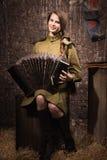 Soldado fêmea soviético no uniforme da segunda guerra mundial com um accordi Imagem de Stock Royalty Free