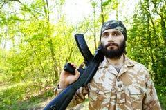 Soldado farpado com um rifle nas madeiras Imagem de Stock