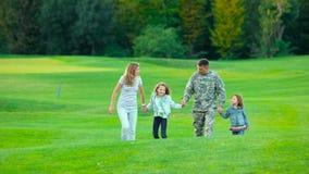 Soldado feliz con su familia en parque almacen de metraje de vídeo