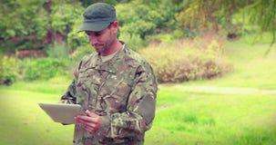 Soldado feliz que usa o tablet pc video estoque