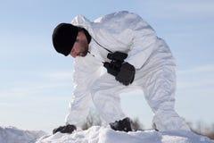 Soldado ferido na camuflagem branca que sneaking com o mountai Foto de Stock