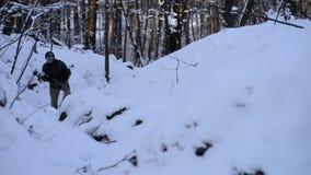Soldado ferido que anda através da neve na floresta filme