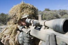 Soldado In Grass Camouflage que señala el rifle Imagen de archivo