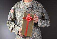 Soldado Holding Christmas Present Imágenes de archivo libres de regalías