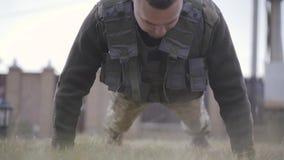 Soldado joven que cae abajo y wrunging hacia fuera del piso en su cierre del chaleco a prueba de balas para arriba El hombre que  almacen de video
