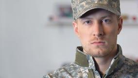 Soldado joven que mira el primer de la cámara, profesión militar, valor, disciplina almacen de video