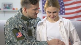 Soldado joven y esposa de la espera que sonríe en la cámara que frota ligeramente el vientre, futuro seguro almacen de metraje de vídeo