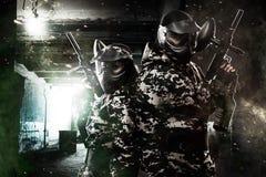 Soldado mascarado fortemente armado do paintball dois no fundo apocalíptico do cargo Conceito do anúncio Foto de Stock