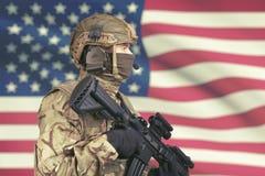 Soldado masculino dos EUA com metralhadora à disposição e bandeira americana no fundo Fotografia de Stock Royalty Free
