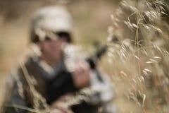 Soldado militar que esconde na grama ao guardar imagem de stock royalty free