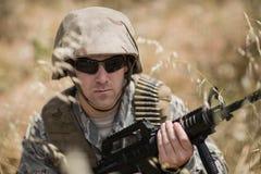 Soldado militar que esconde na grama ao guardar com um rifle foto de stock