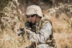 Soldado militar que esconde na grama ao guardar com um rifle fotos de stock royalty free