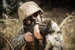 Soldado militar que esconde na grama ao guardar com um rifle foto de stock royalty free