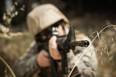 Soldado militar que esconde na grama ao guardar com um rifle fotografia de stock royalty free