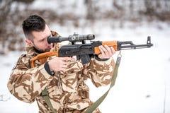 Soldado militar que guarda a arma e que dispara em inimigos no campo de batalha Fotos de Stock
