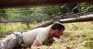 Soldado militar que rasteja sob a rede durante o curso de obstáculo 4k video estoque