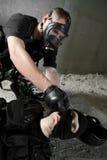 Soldado na máscara de gás que conserva seu sócio ferido Fotografia de Stock Royalty Free