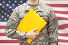 Soldado novo do exército dos EUA que guarda o dobrador amarelo na mão esquerda Imagens de Stock
