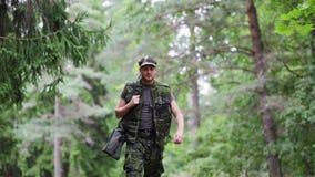 Soldado o cazador joven con el arma en bosque metrajes