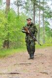 Soldado o cazador joven con el arma en bosque Imagen de archivo libre de regalías