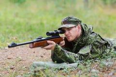Soldado o cazador joven con el arma en bosque Imágenes de archivo libres de regalías