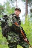 Soldado o cazador joven con el arma en bosque Fotos de archivo libres de regalías