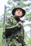 Soldado o cazador joven con el arma en bosque Fotos de archivo