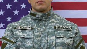 Soldado patriótico que lleva a cabo la mano en el corazón, fondo de la bandera nacional de los E.E.U.U., defensa almacen de metraje de vídeo