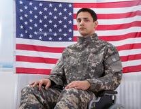Soldado patriótico que se sienta en la silla de rueda contra bandera americana Imagenes de archivo