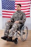 Soldado patriótico que se sienta en la silla de rueda contra bandera americana Imagen de archivo libre de regalías