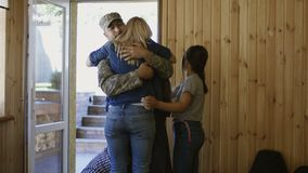 Soldado que entra a casa con la familia feliz metrajes