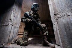 Soldado que esconde em um concreto atrás da tampa onde ajoelhando-se na entrada com uma arma em sua mão Fotos de Stock Royalty Free