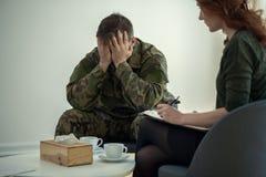 Soldado que esconde sua cara em suas mãos ao falar a um psiquiatra durante a terapia fotografia de stock