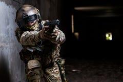 Soldado que guarda uma arma em em seus mão e apontar Foto de Stock